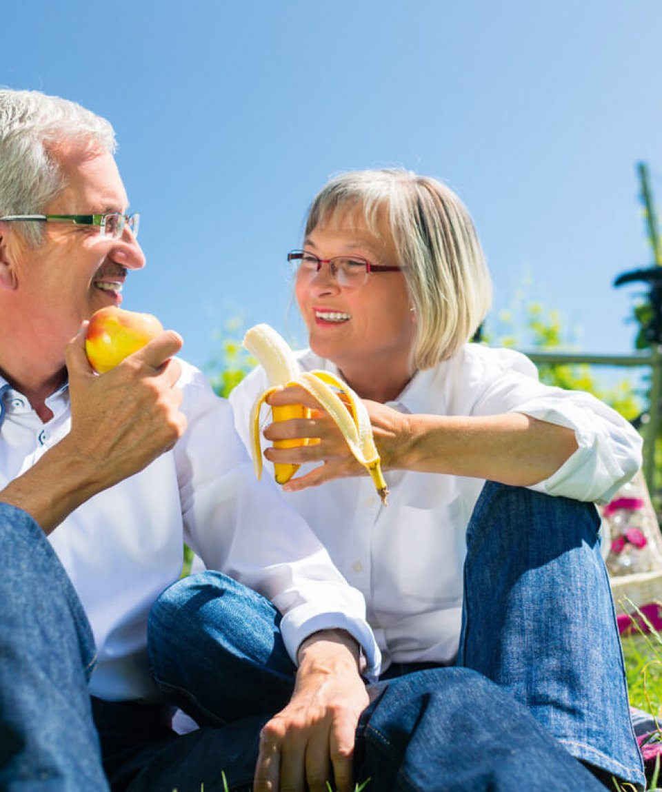 Senior couple eating and drinking at picnic in summer